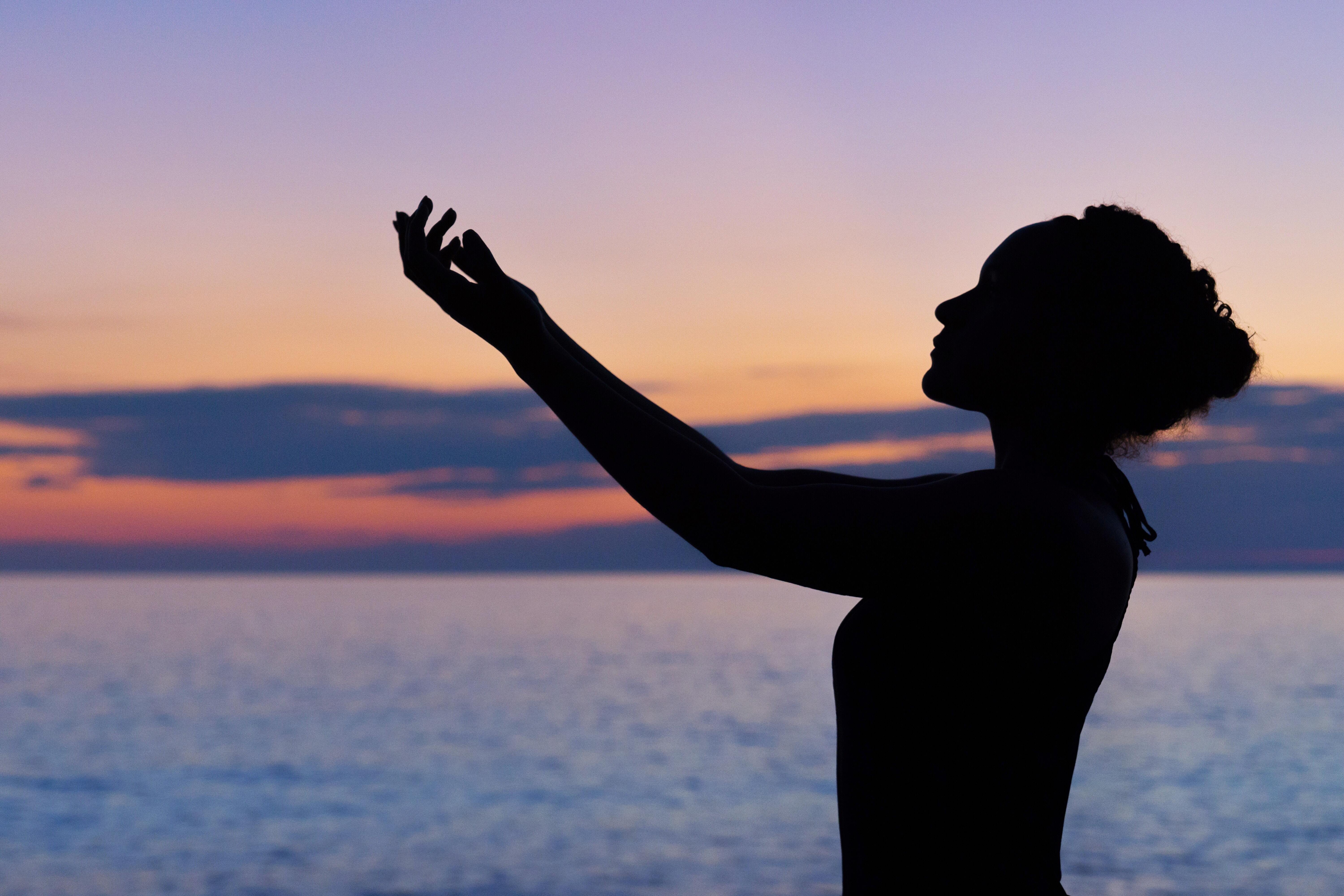 Woman with her hands lifted to the sky in gratitude